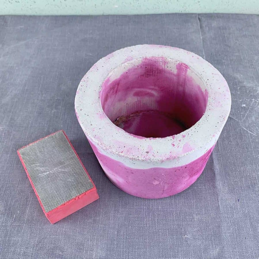 sanding sponge next to vibrantly dyed  concrete planter
