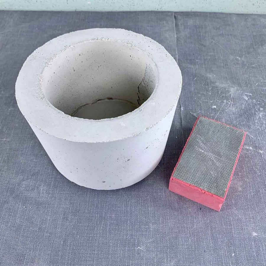 sanding block next to white concrete planter