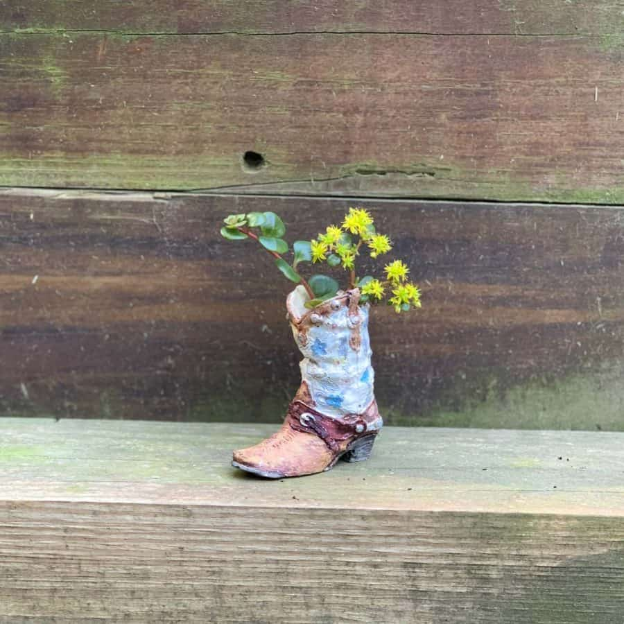 pearly white and tannish/light brown cowboy boot planter with plants inside