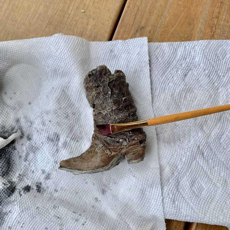 brush painting reddish color of strap onto concrete cowboy boot planter