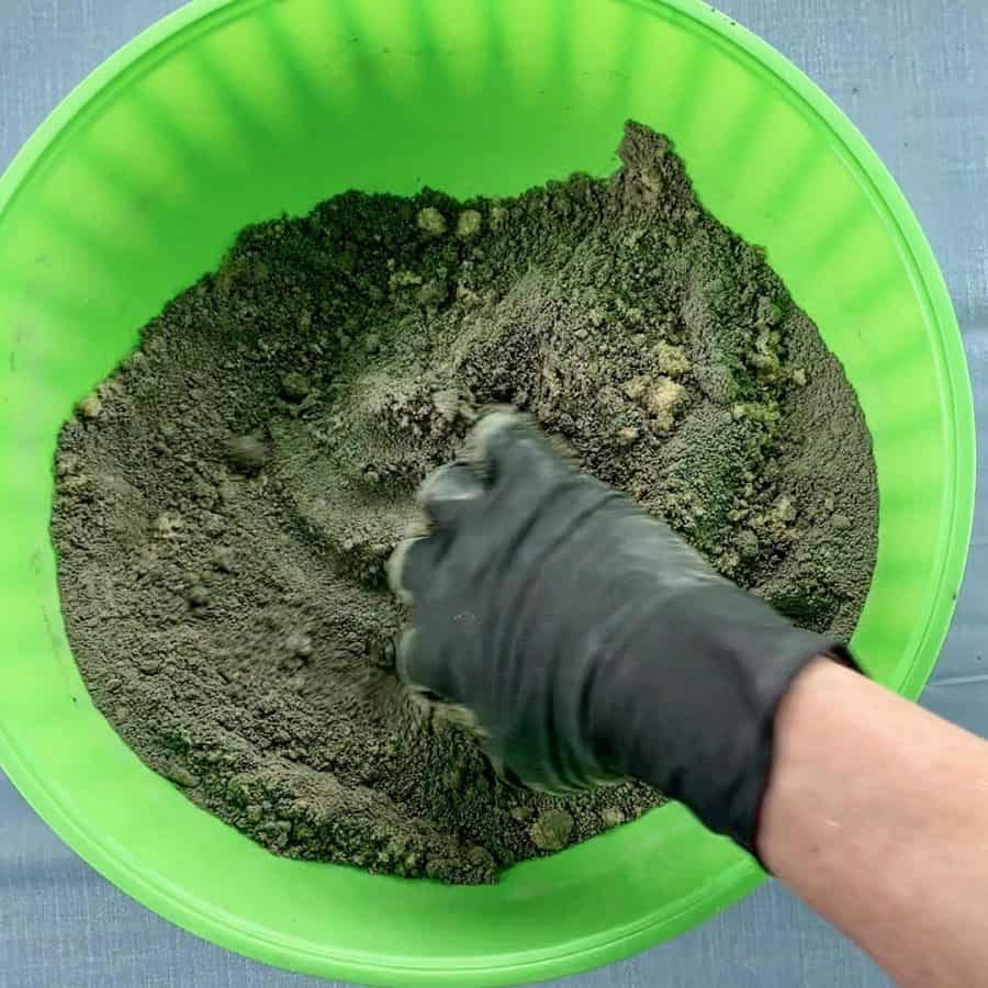 hand mixing cement and sand in bowl