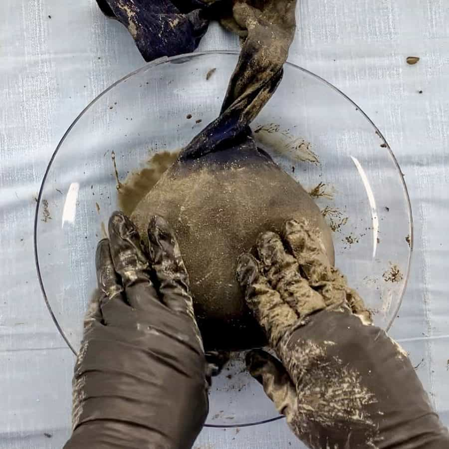 mound of concrete inside of sock laying flat in shallow dish