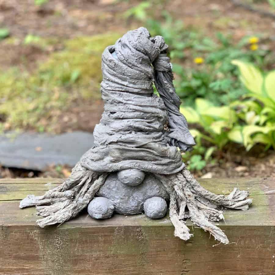 girl concrete gnome on log