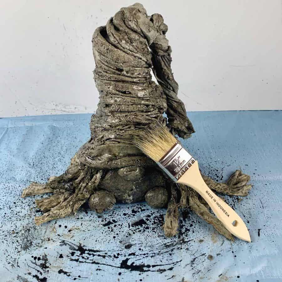 paint brush with black paint on concrete gnome