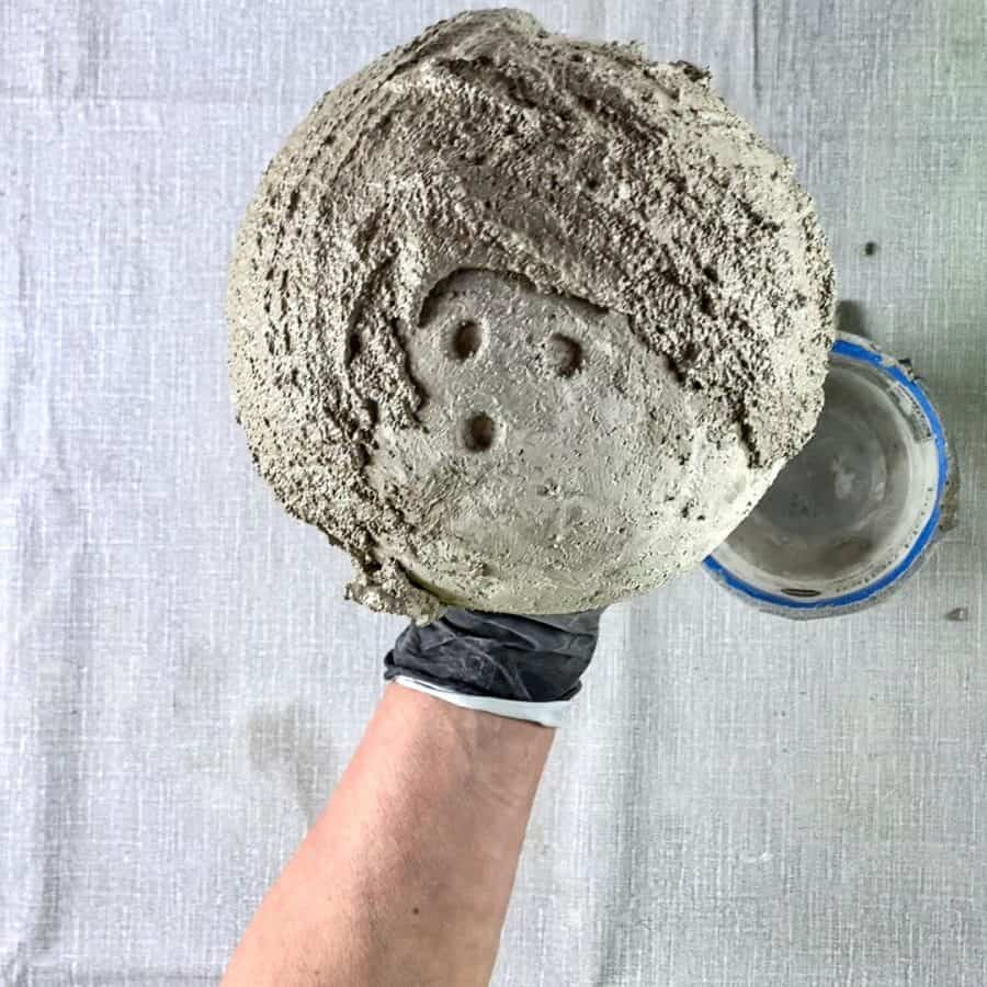 holding cement balloon bowl with 2nd layer of cement slathered on