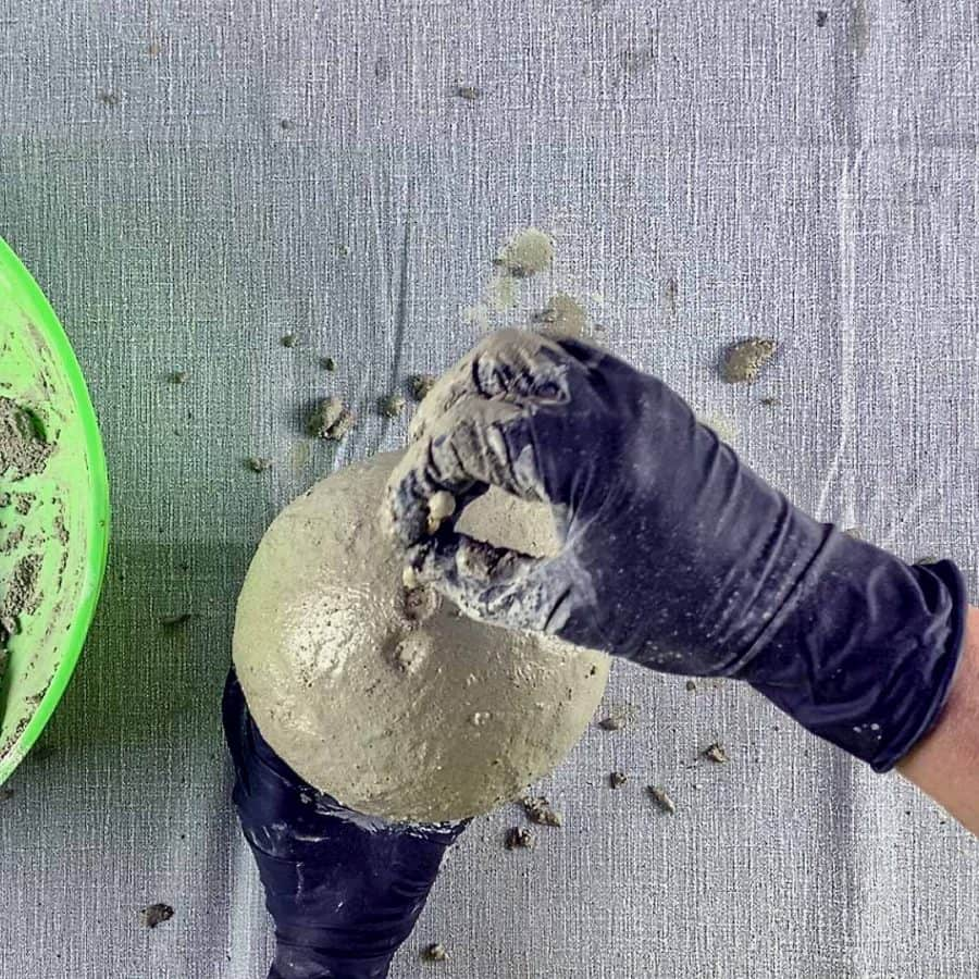 hand pressing holes into cement with q-tip