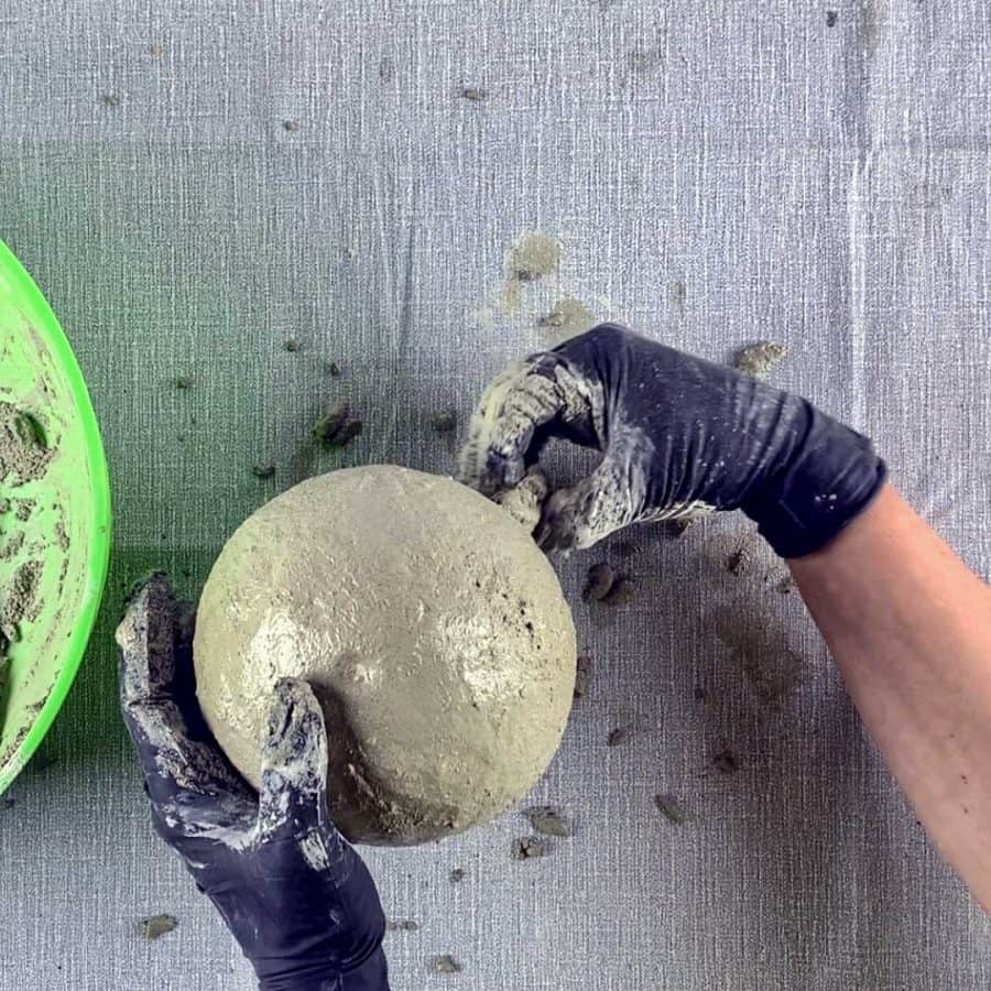 hand pinching cement from bottom of balloon