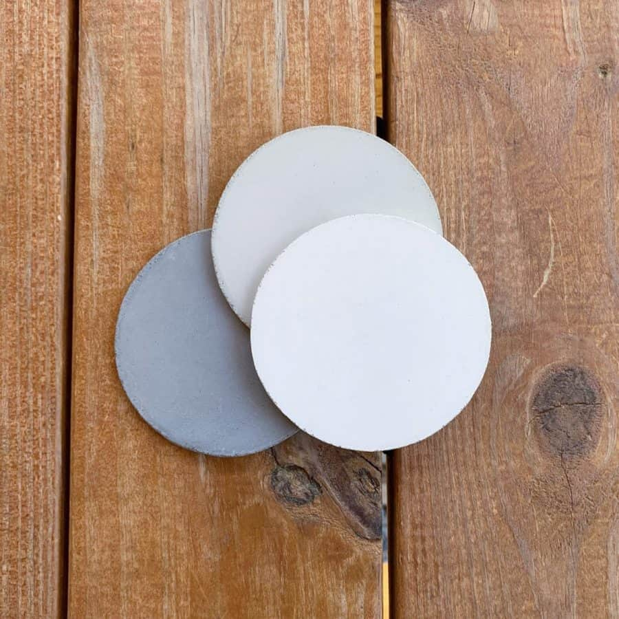 3 concrete coasters next to each other- one white, grey and off-white