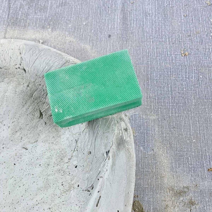 diamond sanding sponge on edge of butterfly puddler to sand concrete where plastic is