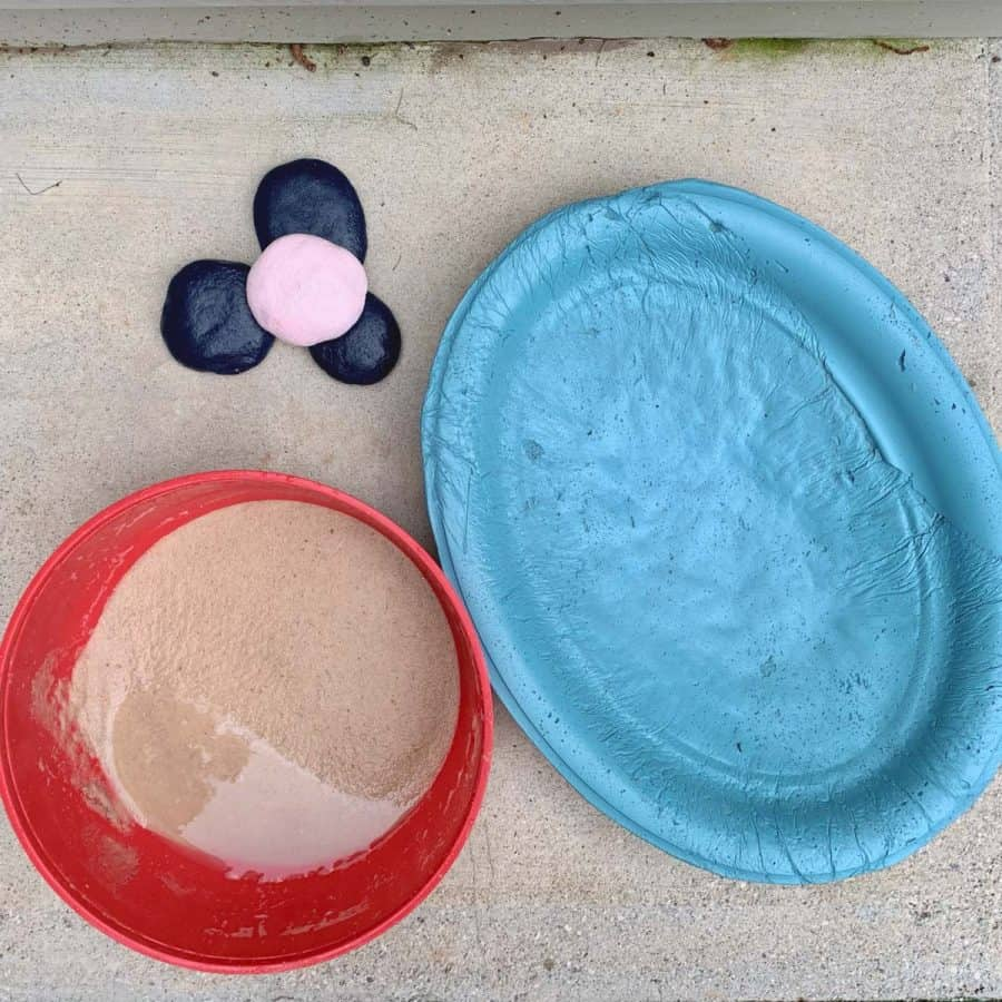 teal concrete butterfly puddler, bowl of wet sand and 3 blue concrete stones, one pink stone