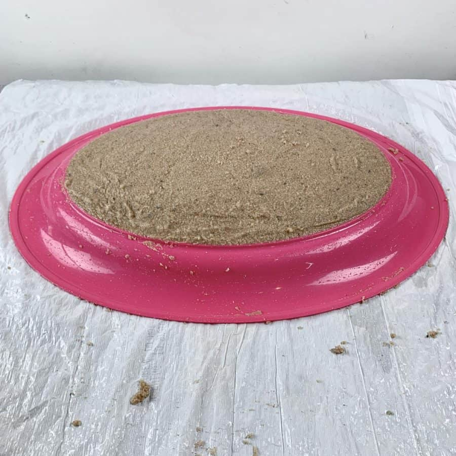 sand neatly molded over top of upside down tray