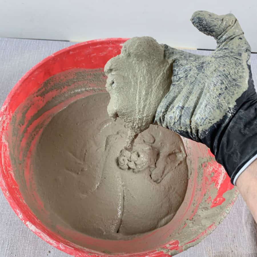 hand with concrete mix slow dripping into bowl