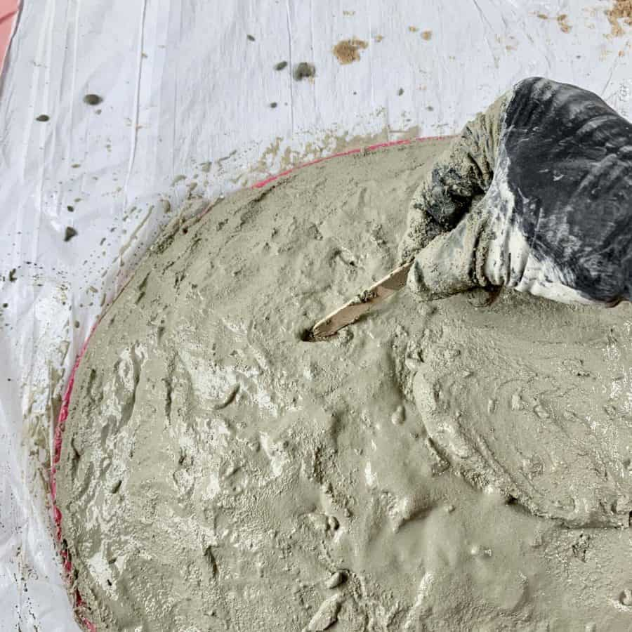 hand scraping away cement with craft stick