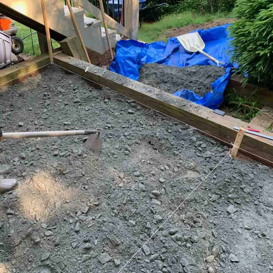 person with hoe pulling on gravel on patio