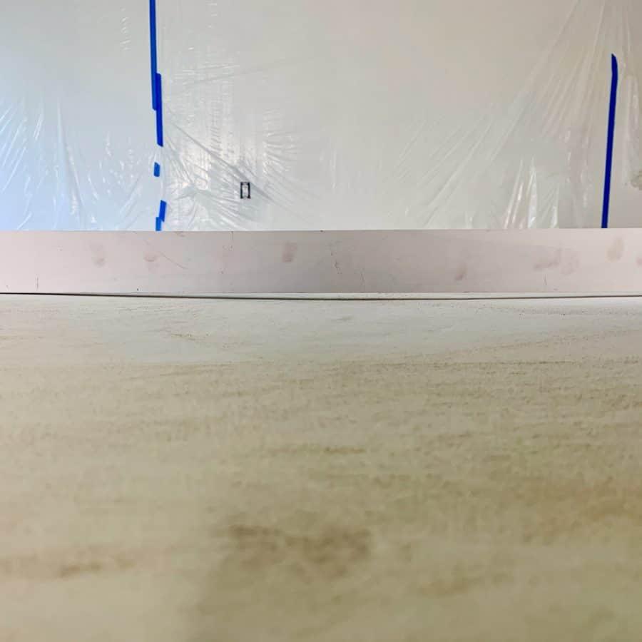 level concrete floor- 1x4 lumbar laying across floor with big gap underneath, showing floor uneven