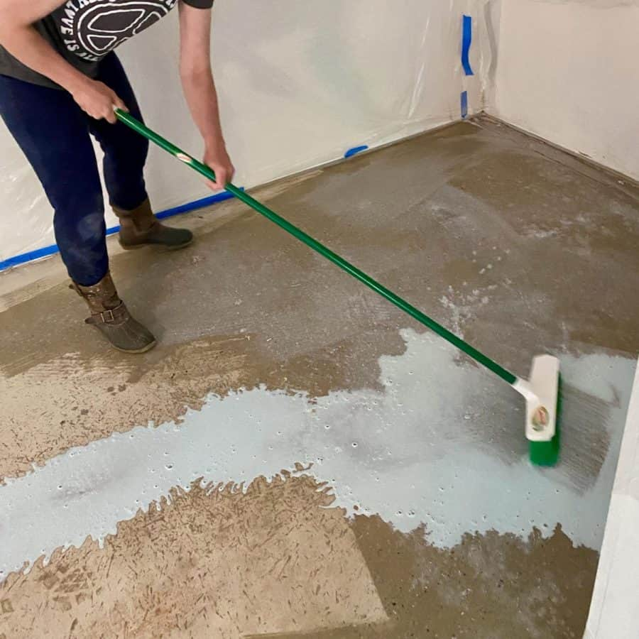 level concrete floor- person holding long handled brush, spreading acrylic primer onto floor