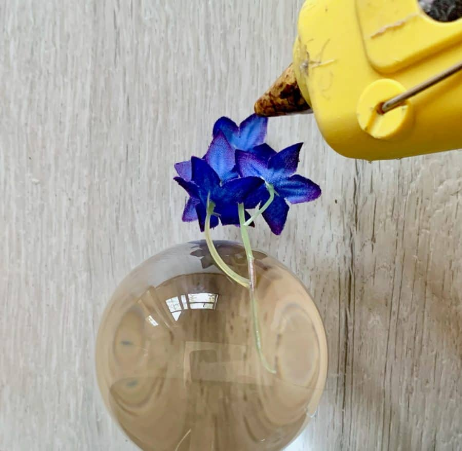 Silicone Sphere Mold- hot glue being applied to purple flowers on a glass ball