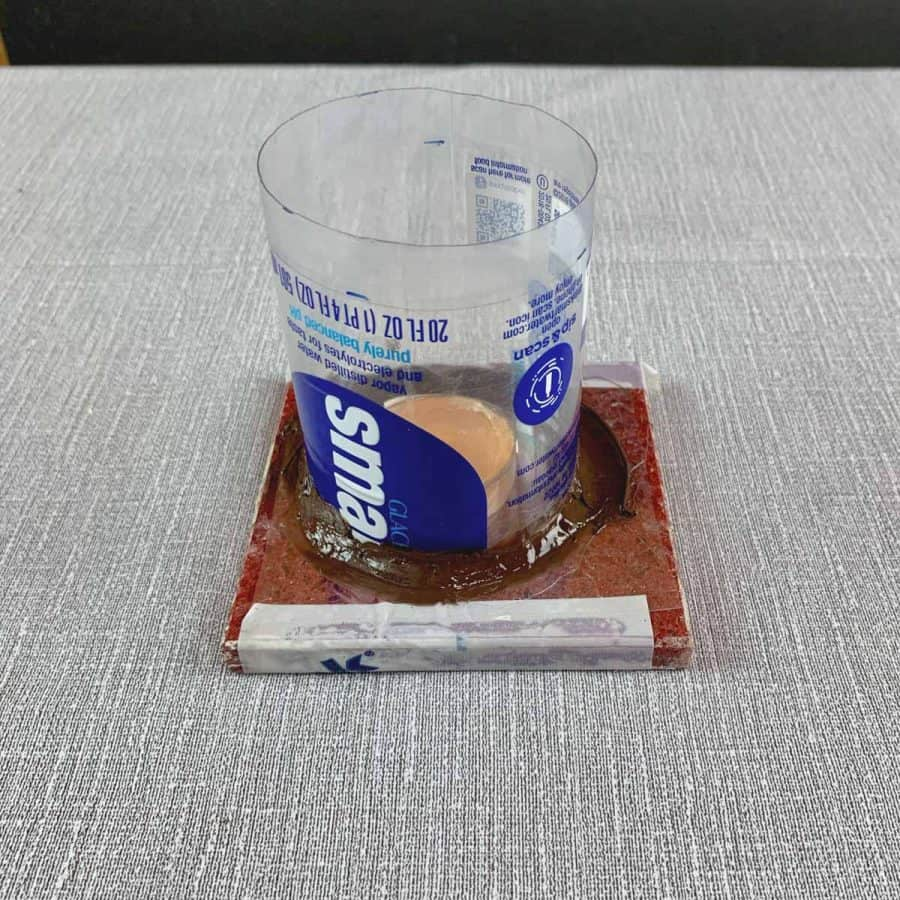 Concrete Candle Holder-tile with acetate films taped to it and water bottle sleeve caulked to it. inside is a tea light candle glued to the bottom.