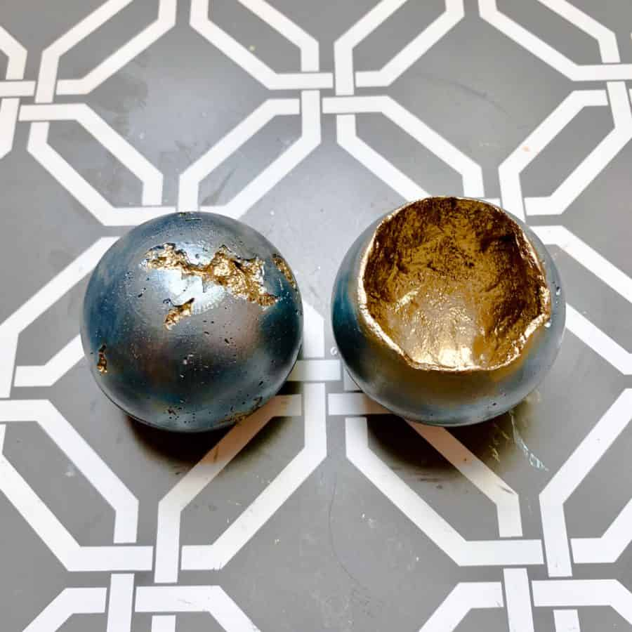 concrete candle- two candle vessels one upside down with pitting showing gold inside the rest of ball is blue. Inside of other ball is gold.