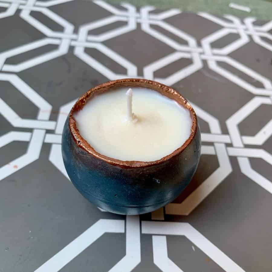 concrete candle with wax hardened and wick trimmed to a little above rim.