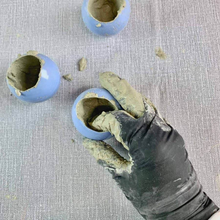 concrete candle- fingers with gloves inside of plastic ball pushing against concrete