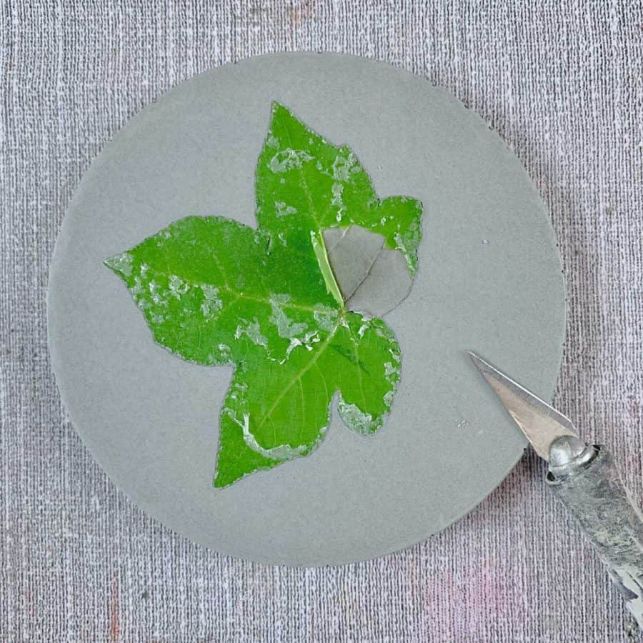 Concrete Coasters- cured coaster with green leaf embedded in it, corner of leaf lifted from concrete and x-acto knife next to it.