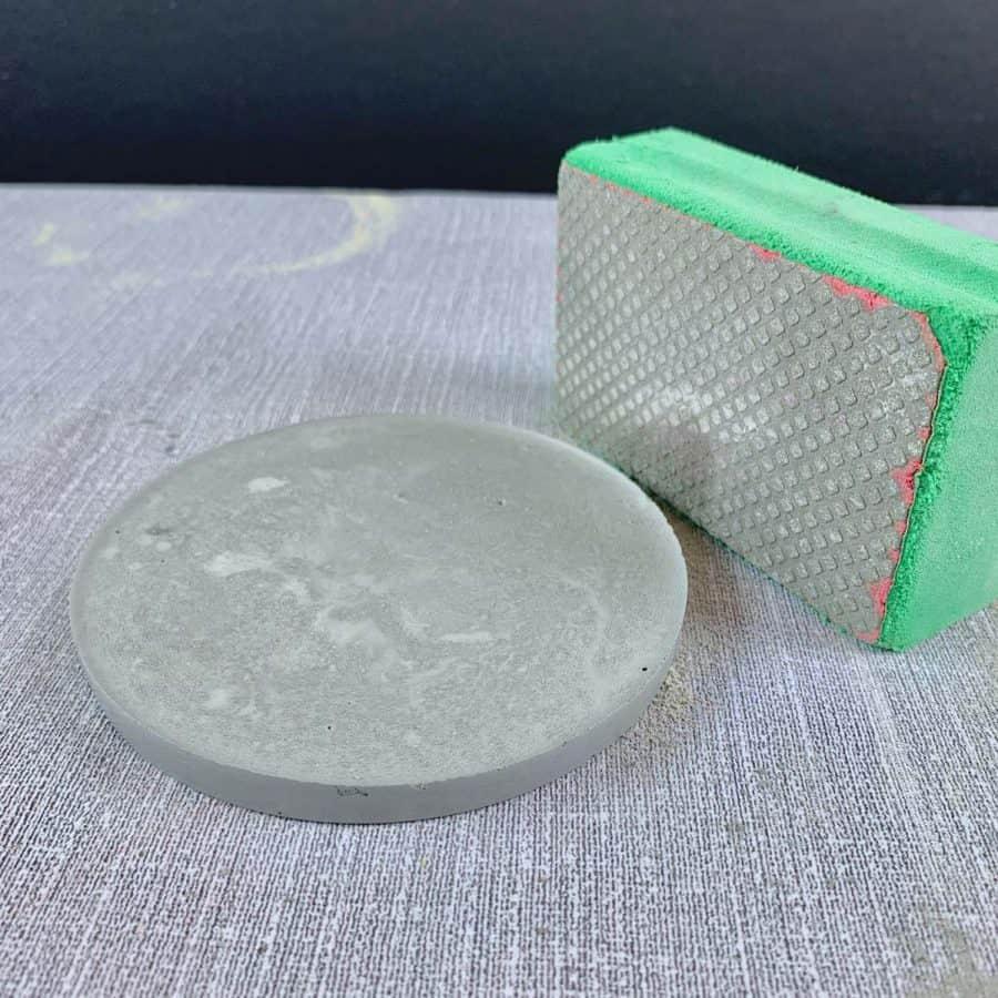 Concrete Coasters-coaster next to diamond sanding sponge. Coaster shows sharp, raised edge.