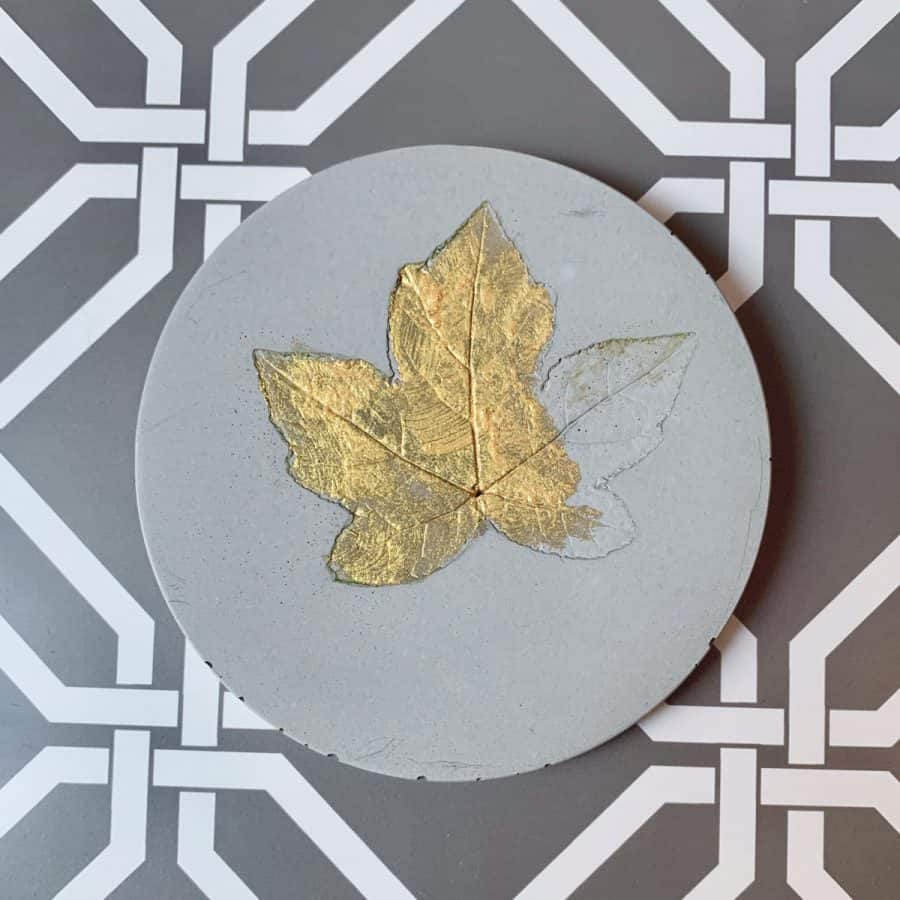 Concrete Coasters- coaster with leaf and partially painted with gold paint.