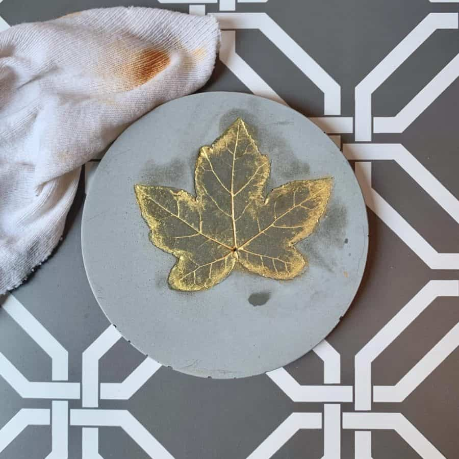 Concrete Coasters-coaster with gold leaf with wet spots and damp cloth next to it.
