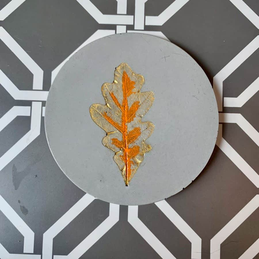 Concrete Coasters-beverage coaster with orange paint in middle, gold paint underneath