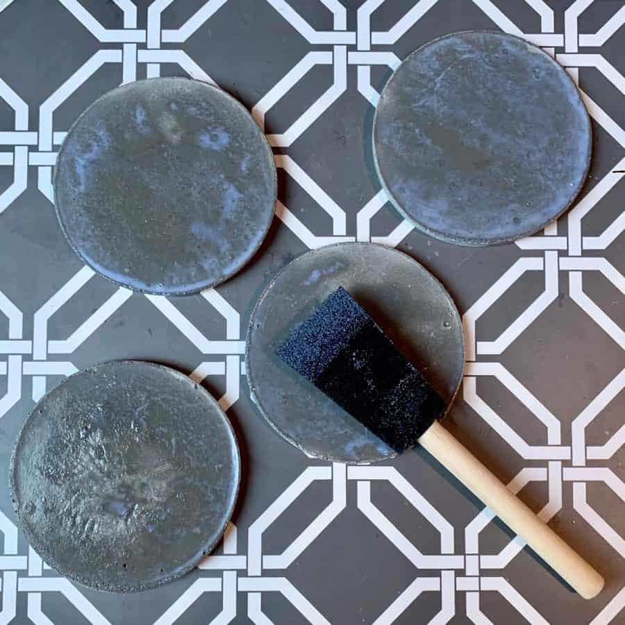 Concrete Coasters-foam brush placing wet sealer onto backs of coasters