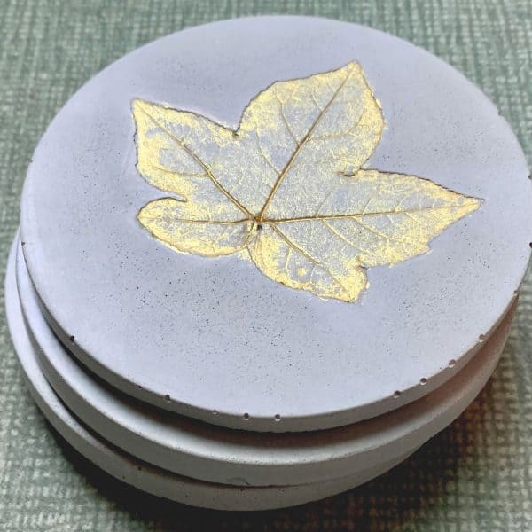 Concrete Coasters-Concrete Coasters- stacked with sweet gum tree leaf imprint, painted gold.