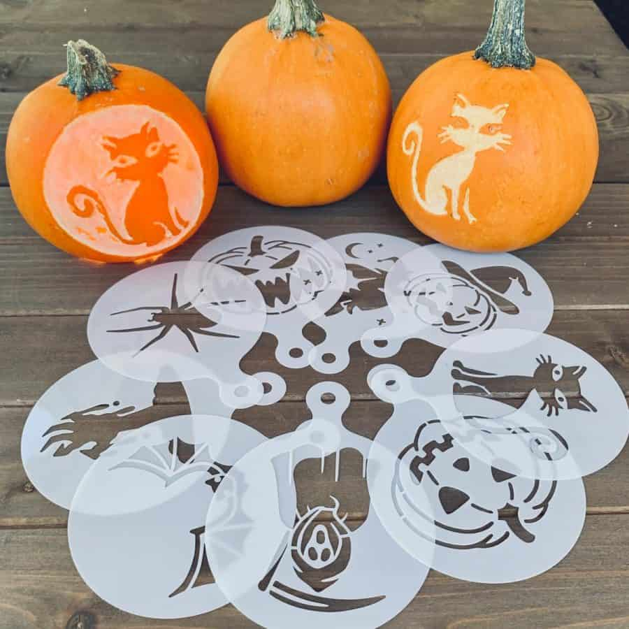 multiple small pumpkin carving stencils in circle in front of 3 mini pumpkins, 2 pumpkins are carved.